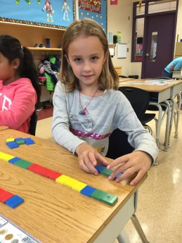 Temprance is building patterns using tiles. She took up most of her table building large, complex patterns.
