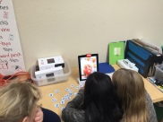 This group is playing a word game with the Osmo. The game involves both letter and picture clues. The students have to try to create the word on the table using letter tiles, before the other.