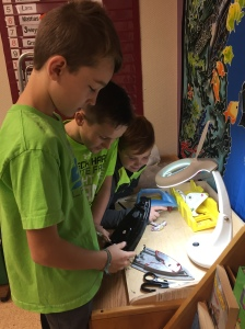 Ashton, Turner and Jordan are busy taking apart an iron at the tinker station.